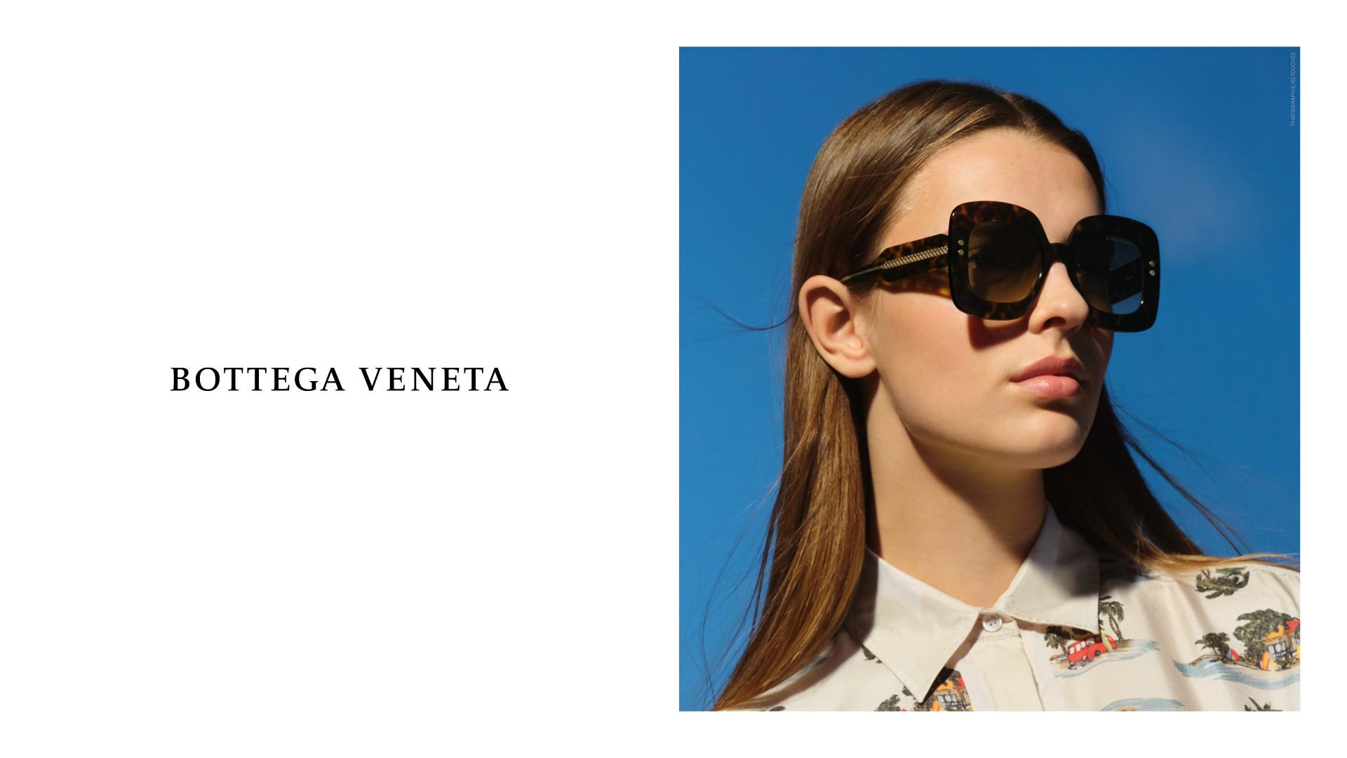 Aufnahme mit blauem Hintergrund von einem weiblichen Model mit braunen Haaren, das eine schwarze Sonnenbrille von Bottega Veneta trägt.