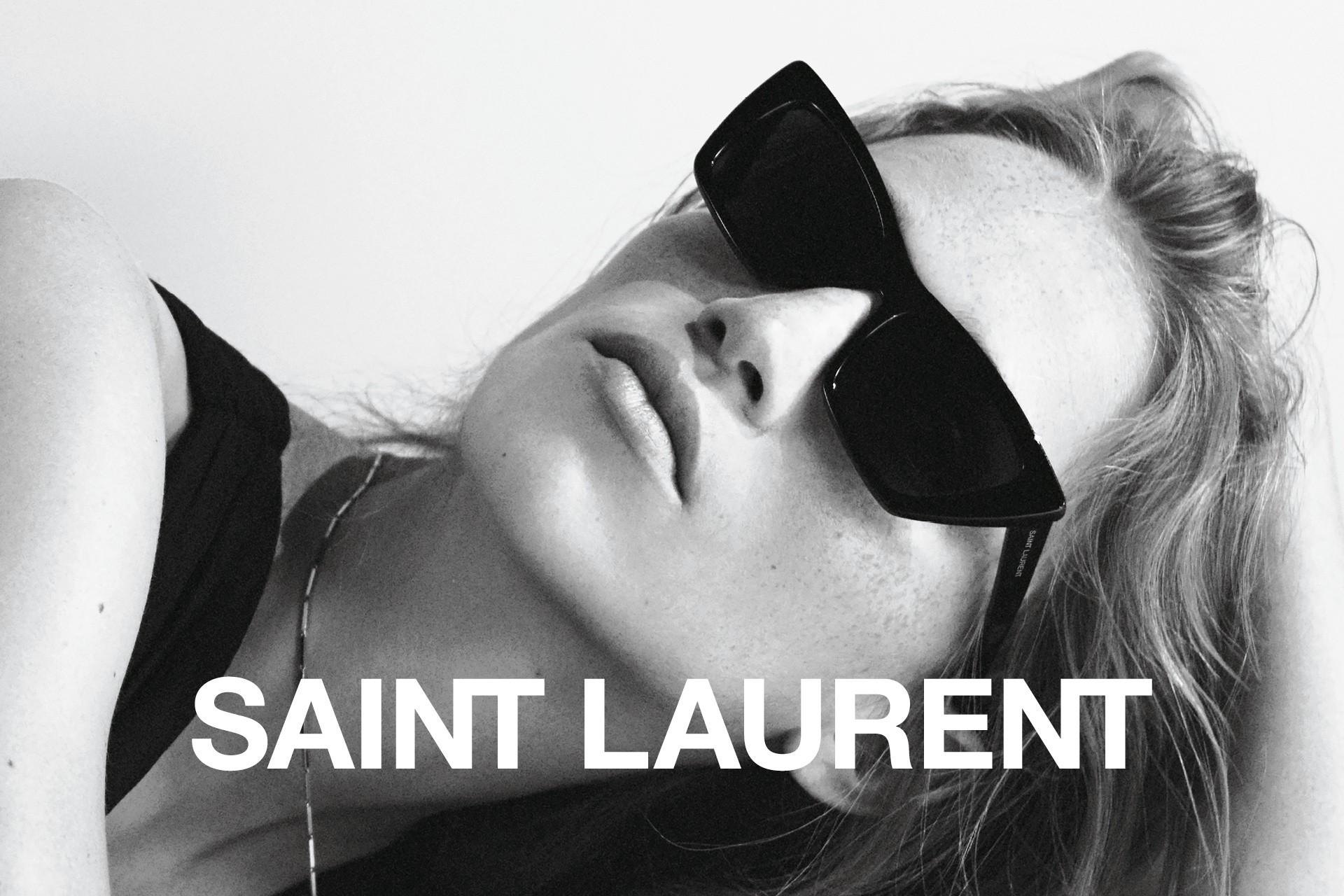 Schwarz-weiße Nahaufnahme von einem weiblichen Model, das eine schwarze Saint Laurent Sonnenbrille trägt.