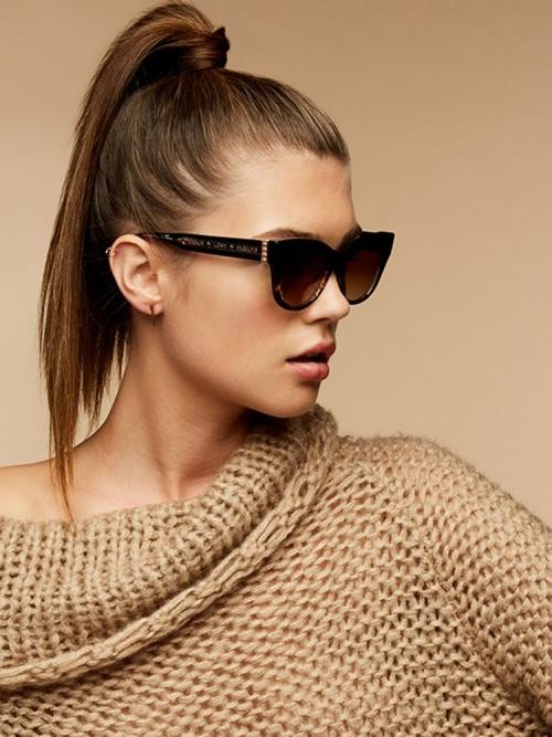 Nahaufnahme mit beigem Hintergrund von einem Female Model, das eine Shamballa Sonnenbrille trägt.