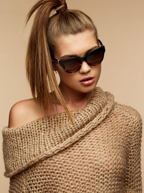 Beigefarbenes Foto von einem weiblichen Model mit hellbraunen Haaren, das eine Brille von Paradis Collection trägt.