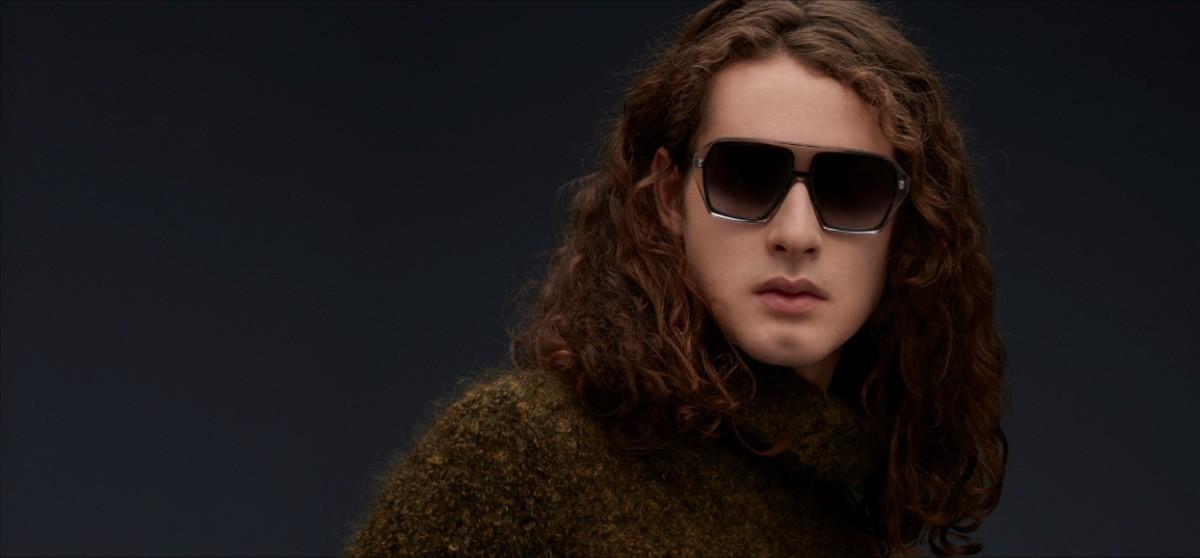 Nahaufnahme von einem Mann mit langen, braunen Haaren, der eine dunkle Blake Kuwahara Sonnenbrille trägt.