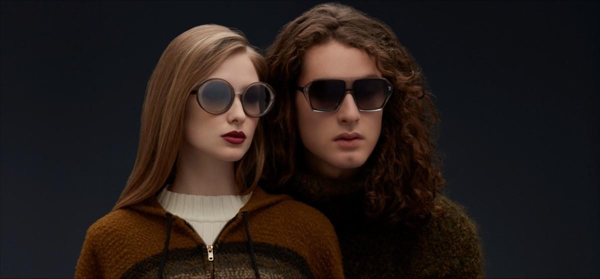 Nahaufnahme mit schwarzem Hintergrund von einer Frau mit rötlichen Haaren und einem Mann mit langen Haaren, die Blake Kuwahara Sonnenbrillen tragen und in die Ferne schauen.