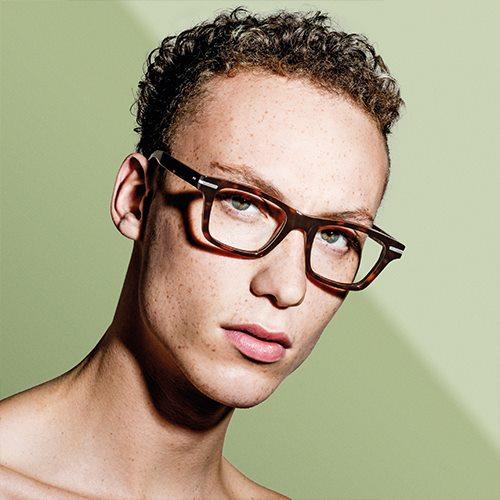 Nahaufnahme mit grünem Hintergrund von einem Mann mit Sommersprossen und braunen Locken, der eine braune Cutler and Gross Korrekturbrille trägt.