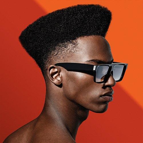 Aufnahme mit neon-orangen Hintergrund von dem seitlichen Profil eines dunkelhäutigen Male Models, das eine schwarze Sonnenbrille mit breiten Bügeln trägt.