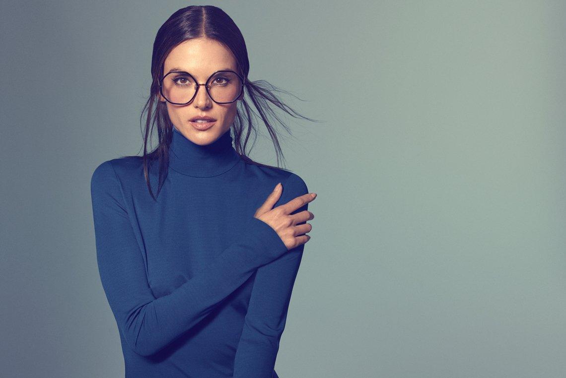 Dunkelhaarige Frau mit blauem Rollkragenpullover posiert mit einer großen, runden Korrekturbrille von Linda Farrow vor der Kamera.