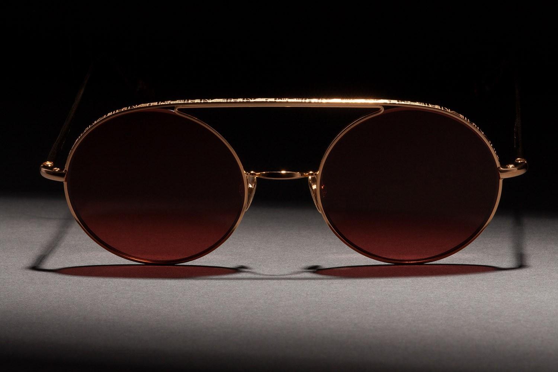 Frontaufnahme von einer Ahlem Brille mit goldenem Rahmen und braunen Brillengläsern.
