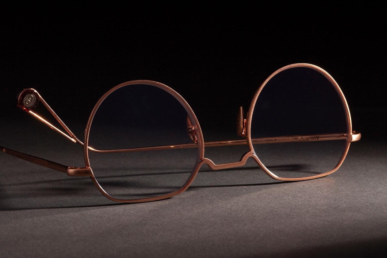 Nahaufnahme von einer goldenen Ahlem Brille, die falsch herum auf dem Boden liegt.