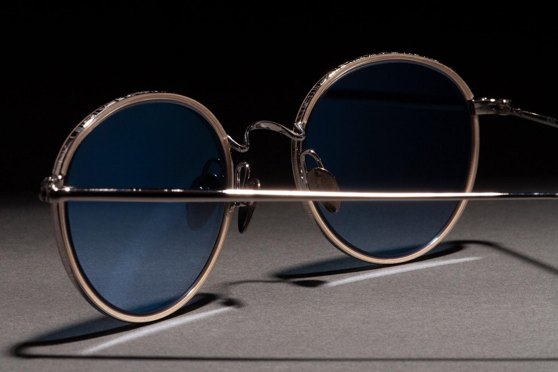 Nahaufnahme von einer Ahlem Fassung mit goldenem Rahmen und bläulichem Brillenglas.