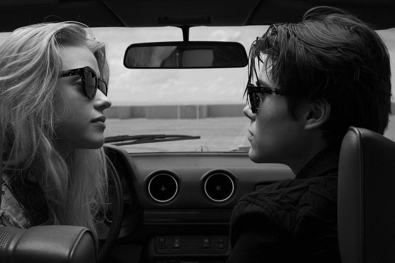 Schwarz-weiß Aufnahme von einem Male Model und einem Female Model, die sich im Auto gegenüber sitzen und eine Ahlem Sonnenbrille tragen.