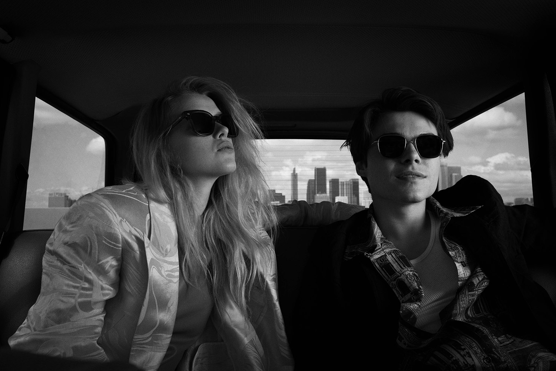 Schwarz-weiße Aufnahme von einem weiblichen und einem männlichen Model im Auto, die dunkle Sonnenbrillen tragen.