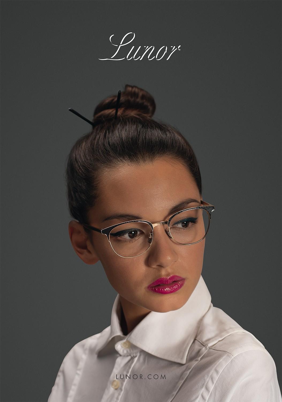 Nahaufnahme von einem braunhaarigen Female Model mit Dutt, das eine Lunor Korrekturbrille trägt.
