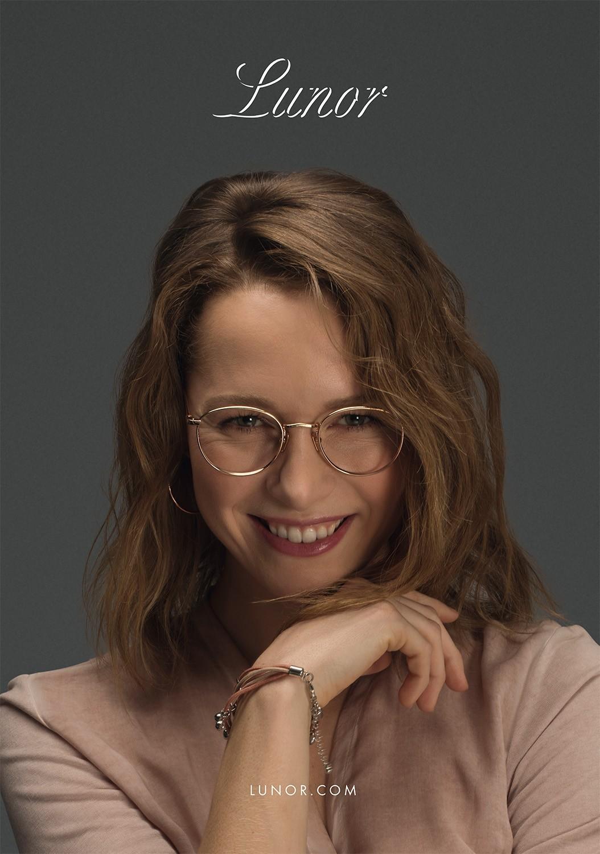 Nahaufnahme von einem lächelnden Female Model mit schulterlangen Haaren, das eine goldene Lunor Korrekturbrille trägt.