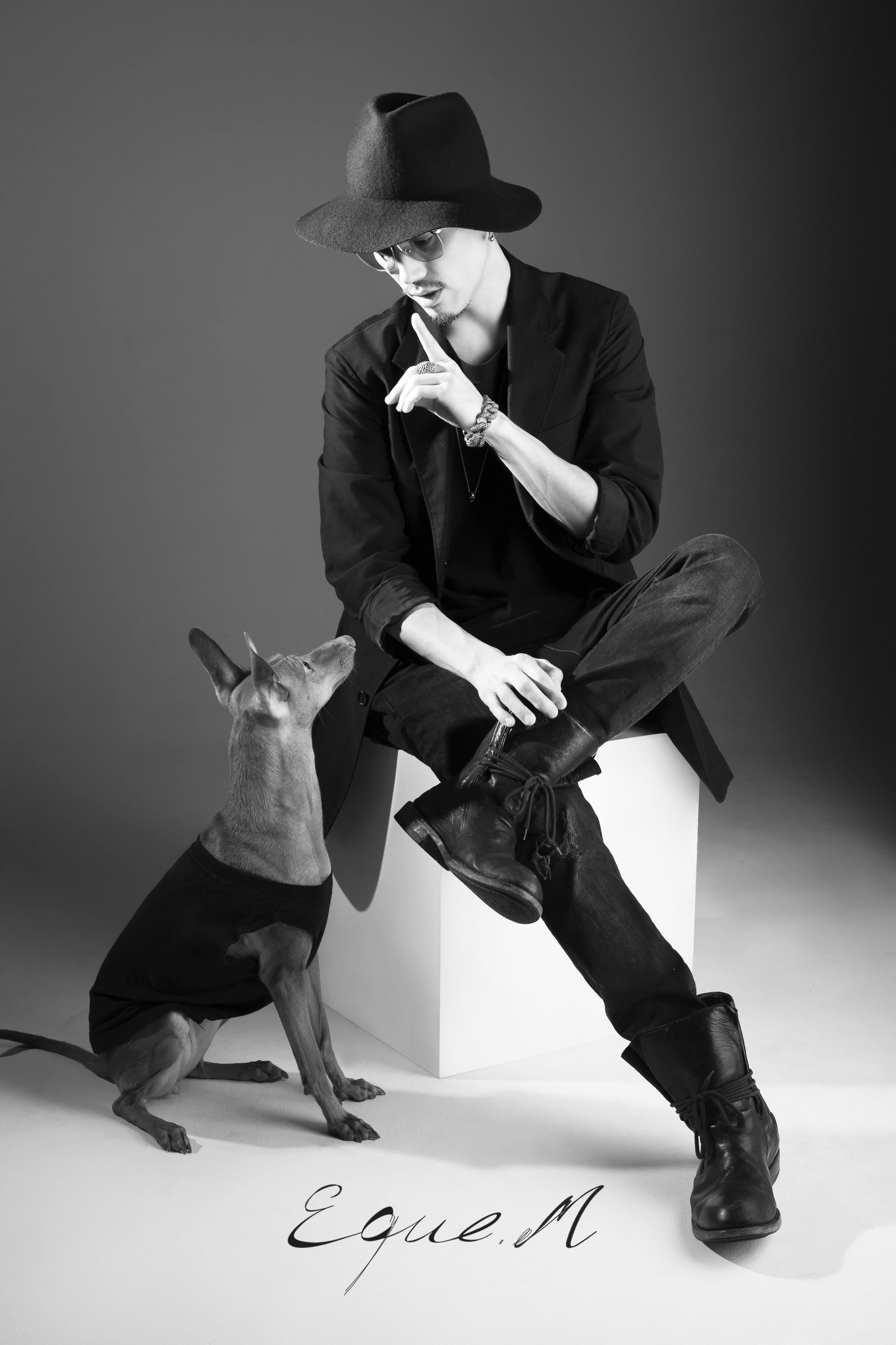 Schwarz-weiß Aufnahme von einem Mann mit schwarzer Kleidung und Hut, mit dem Blick zu einem auf dem Boden sitzenden Hund gerichtet.