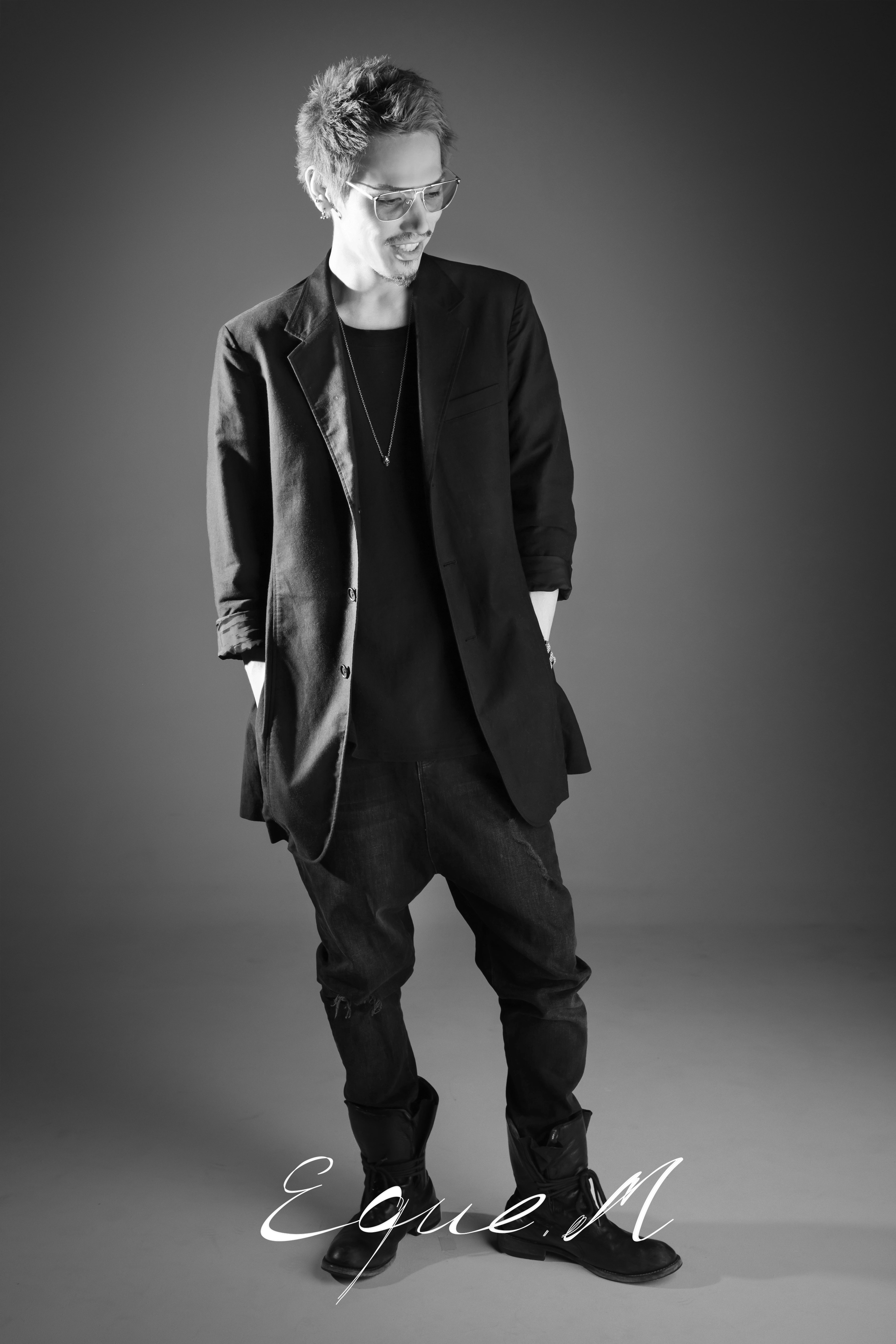 Schwarz-weiß Aufnahme von einem männlichen Model in schwarzer Kleidung und Händen in den Hosentaschen und Blick auf den Boden gesenkt.