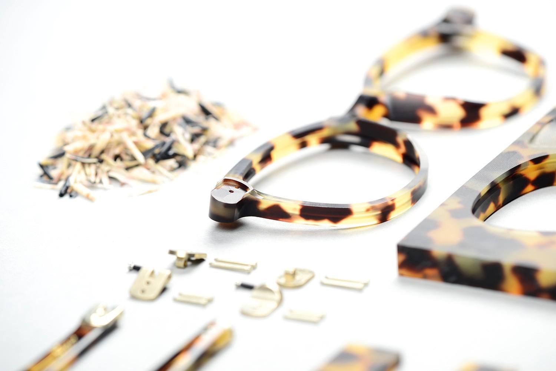 Ein gemustertes Brillengehäuse, Bügel und Schrauben liegen auf einem weißen Untergrund.