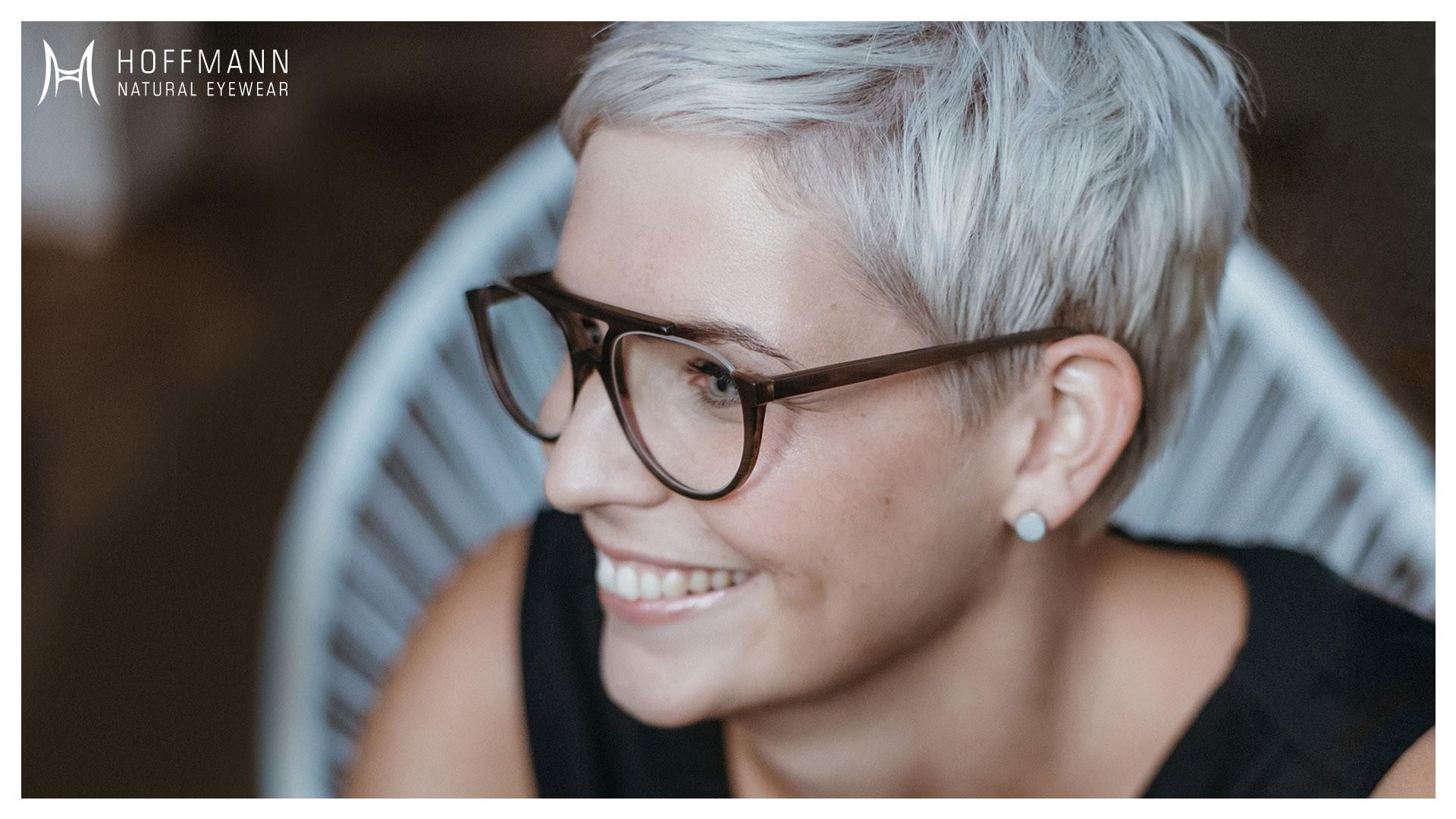 Nahaufnahme von einem lächelndem Female Model mit kurzen, blonden Haaren, das eine Korrekturbrille mit braunem Gestell von Hoffmann Natural Eyewear trägt.