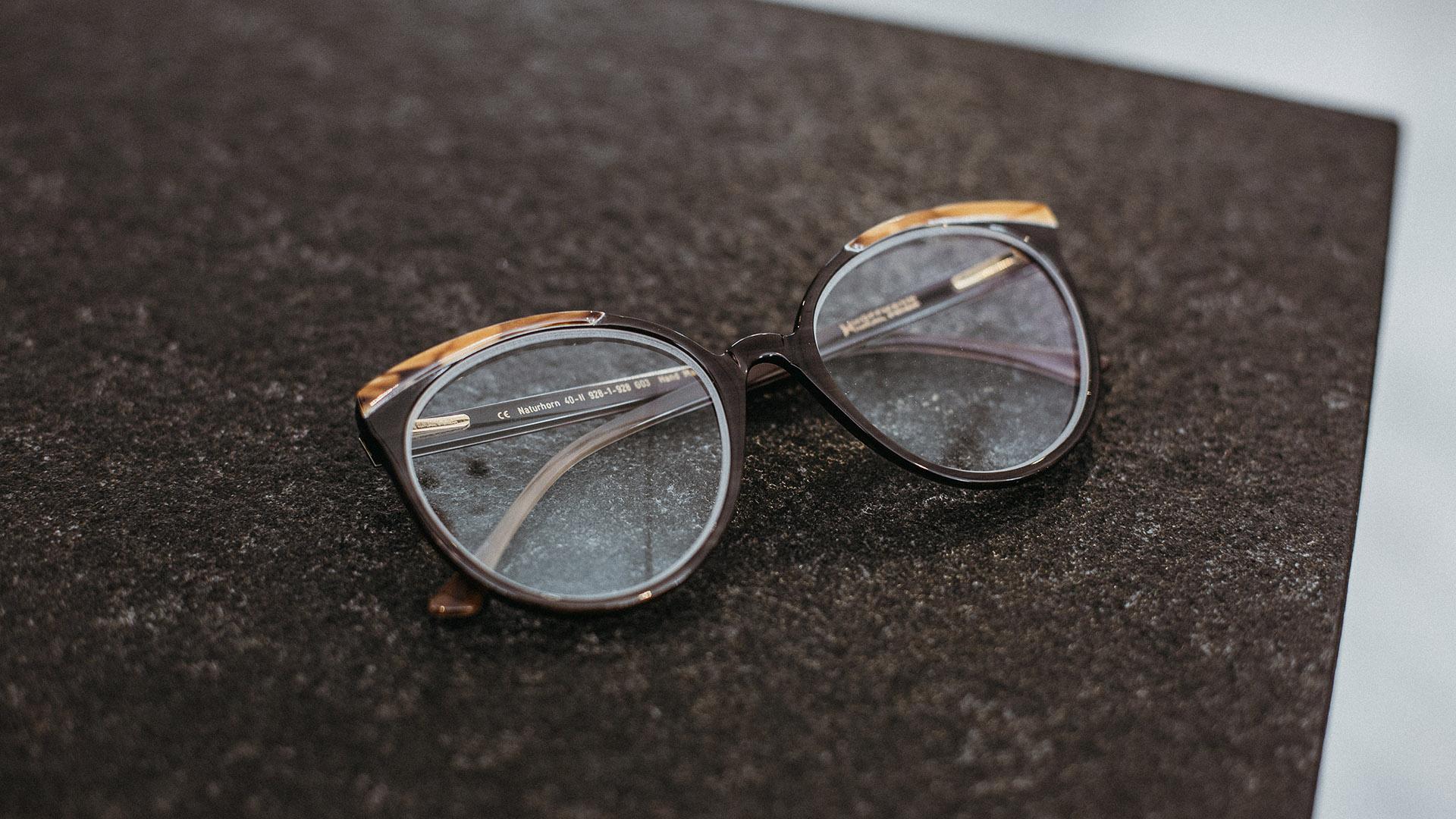 Braune Naturhornbrille mit hellen Akzenten von Hoffmann Natural Eyewear, die auf einem braunen Untergrund liegt.