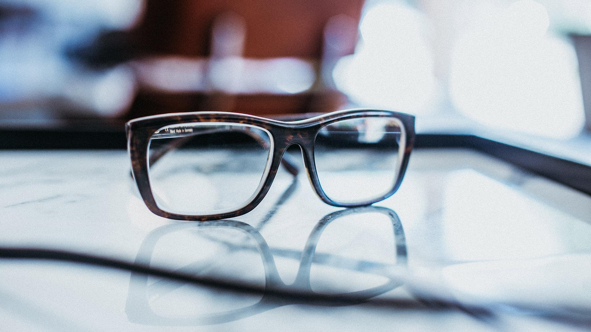 Nahaufnahme von einer braunen Naturhornbrille von Hoffmann Natural Eyewear, die auf einem spiegelnden Glastisch liegt.