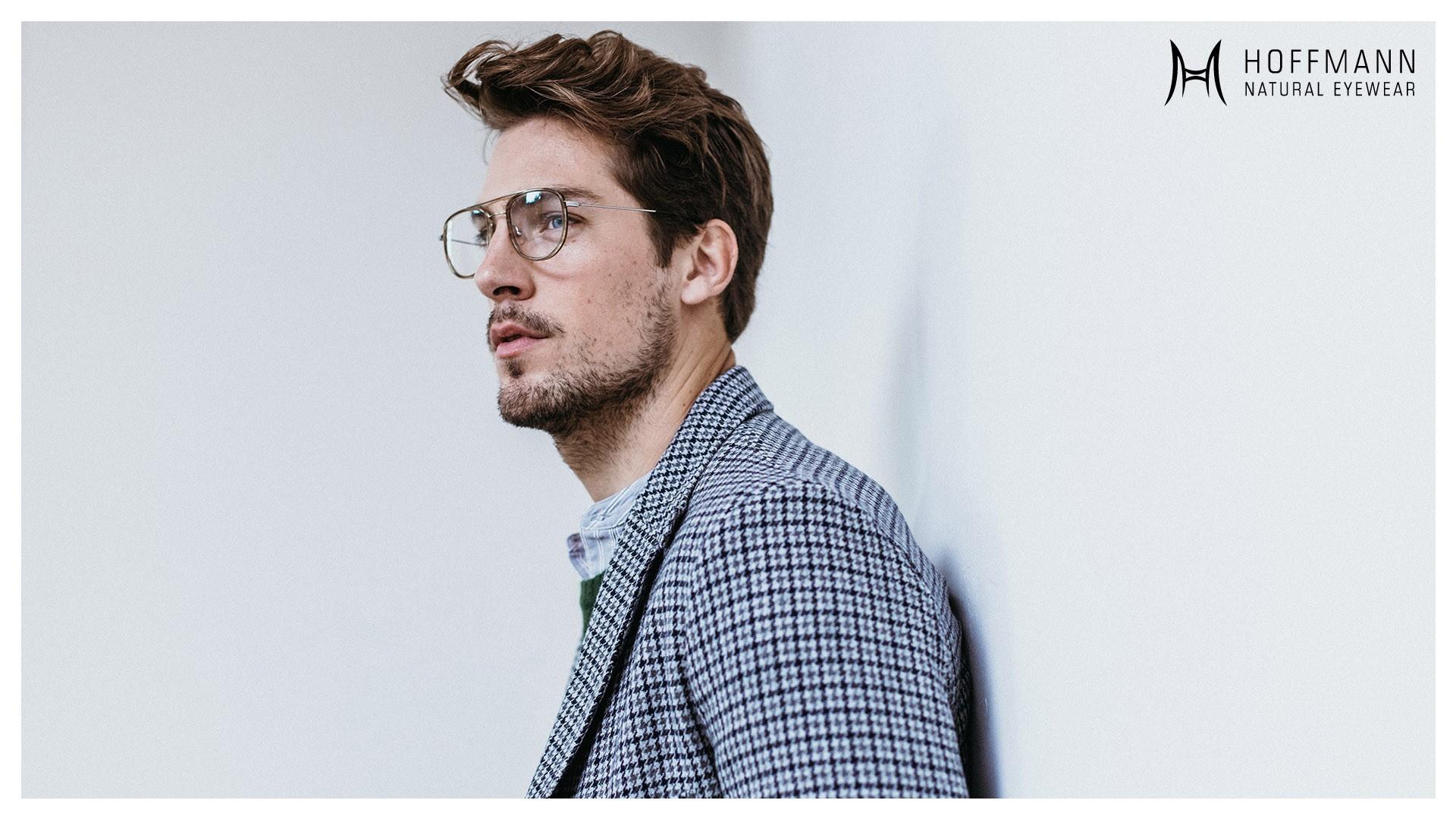 Seitliche Aufnahme von einem Male Model mit braunen Haaren und Bart, das eine Korrekturbrille von Hoffmann Natural Eyewear trägt.