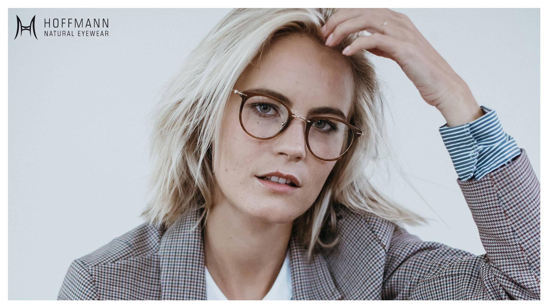 Nahaufnahme von einem Female Model mit schulterlangen Haaren, das einen Blazer und eine runde, braune Fassung von Hoffmann Natural Eyewear trägt.