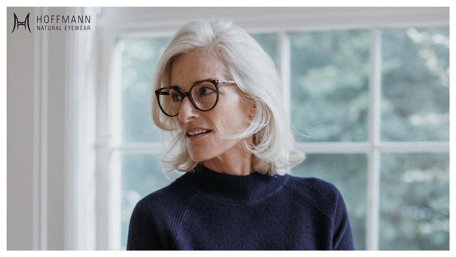 Nahaufnahme von einem älteren Female Model mit schulterlangen, weißen Haaren vor einem Fenster stehend, das eine braune Hoffmann Natural Eyewear Brille trägt.