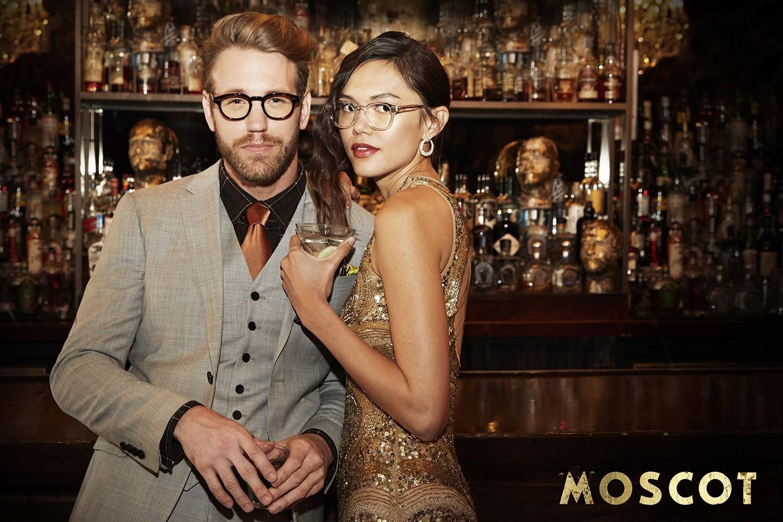 Aufnahme von einer Lounge Party mit einem weiblichen und einem männlichen Model, die an einer Bar stehen.