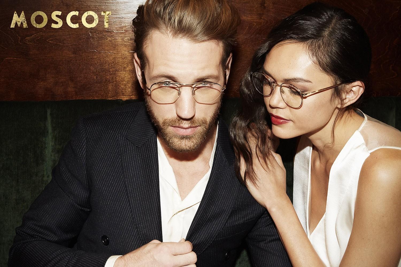 Ein Male Model im Anzug links und ein Female Model mit weißem Satinkleid rechts posieren mit Moscot Brillen.