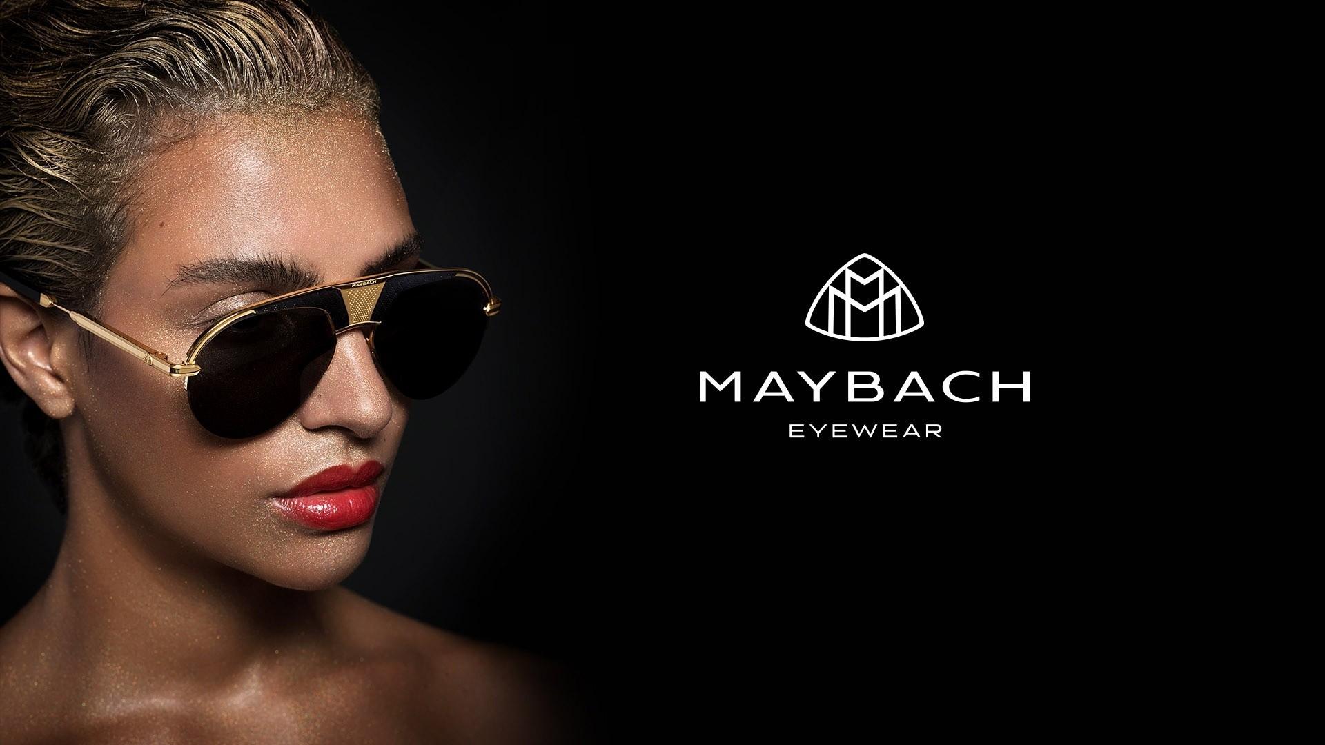 Nahaufnahme von einem Female Model in der linken Bildhälfte, das eine Maybach Sonnenbrille mit goldenen Details trägt und rechts großes Maybach Eyewear Logo.