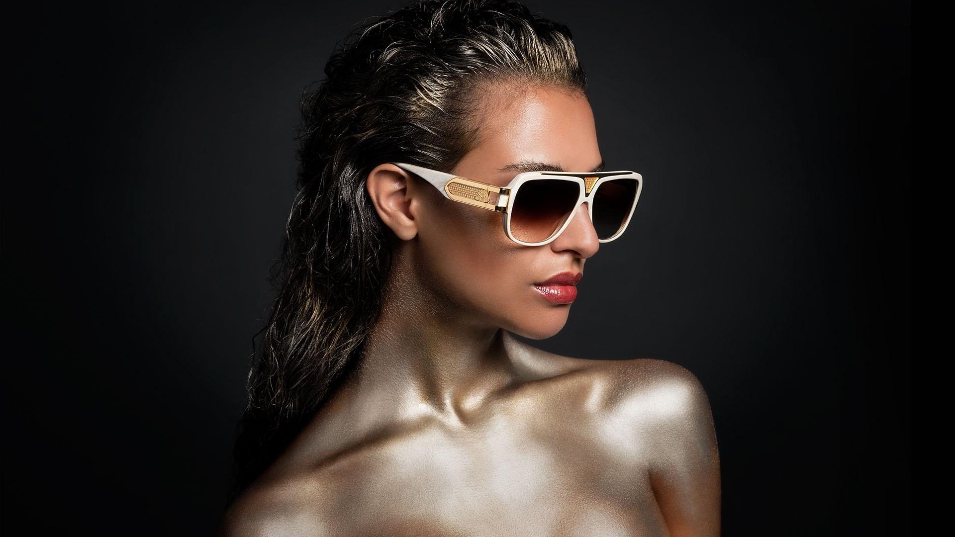 Aufnahme von einem weiblichen Model mit einer weißen Maybach Sonnenbrille mit goldenen Details und schwarzem Hintergrund.