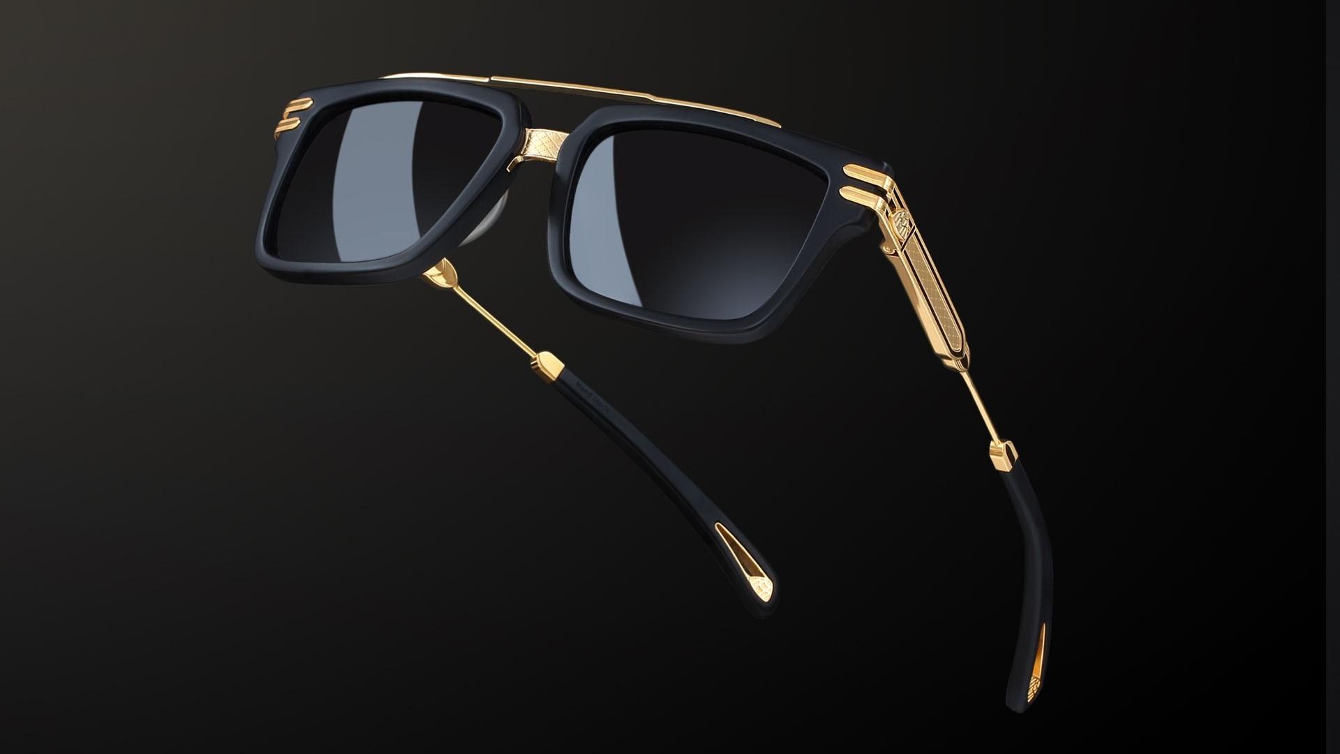 Nahaufnahme von einer Maybach Sonnebrille mit goldenen Details und schwarzem Hintergrund.