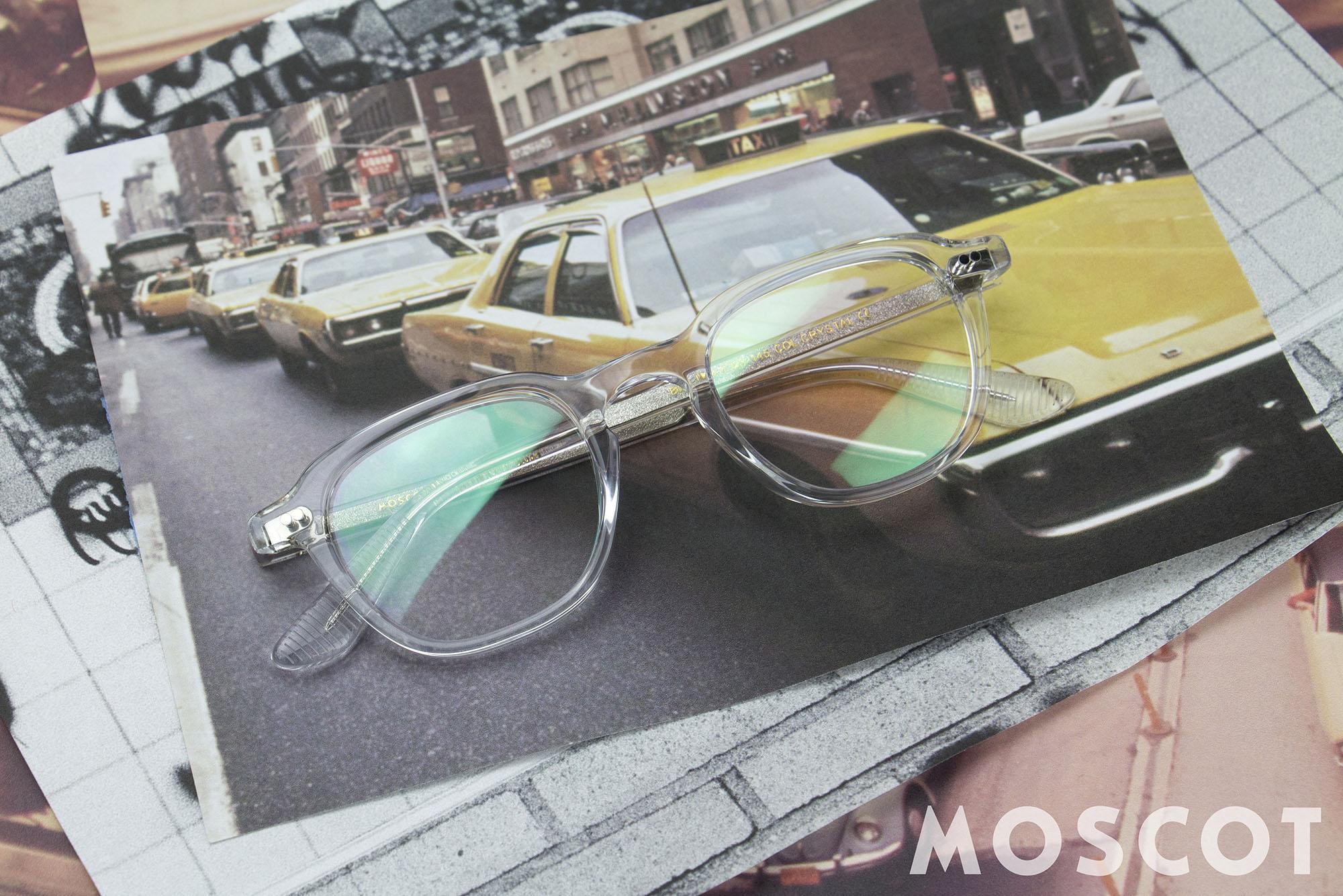 Moscot Korrekturbrille mit durchsichtigem Rahmen, die auf mehreren Fotoausdrücken liegt.