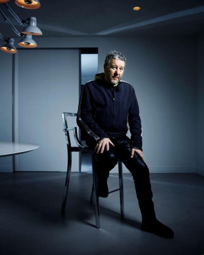 Philippe Starck, der in einem dunkeln Raum auf einem Stuhl sitzt und in die Kamera blickt.