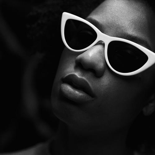 Schwarz-weiße Nahaufnahme von einem weiblichen Model, das eine Ralph Vaessen weiße Sonnenbrille trägt.