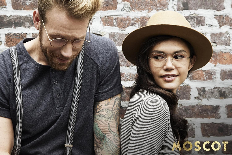 Ein weibliches Model rechts und ein männliches Model links tragen Moscot Eyewear stehen vor einer Bausteinwand.