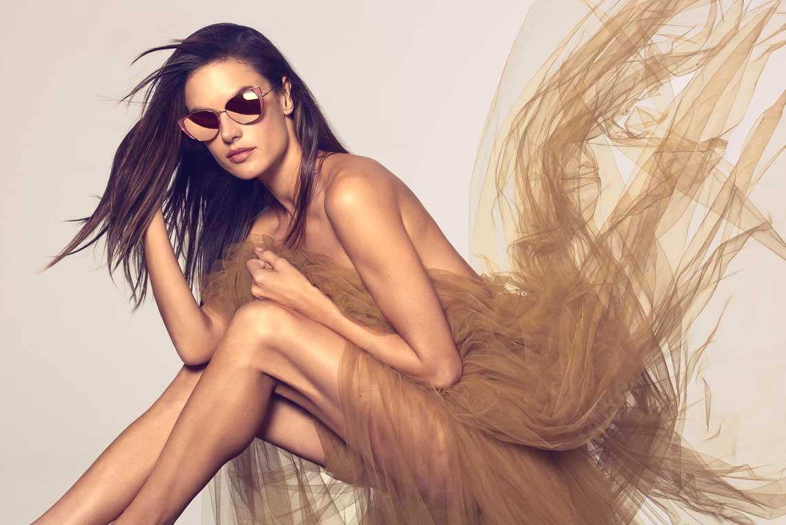 Braunhaarige Frau mit hellbraunem Tüllkleid und goldener Sonnenbrille von Linda Farrow.