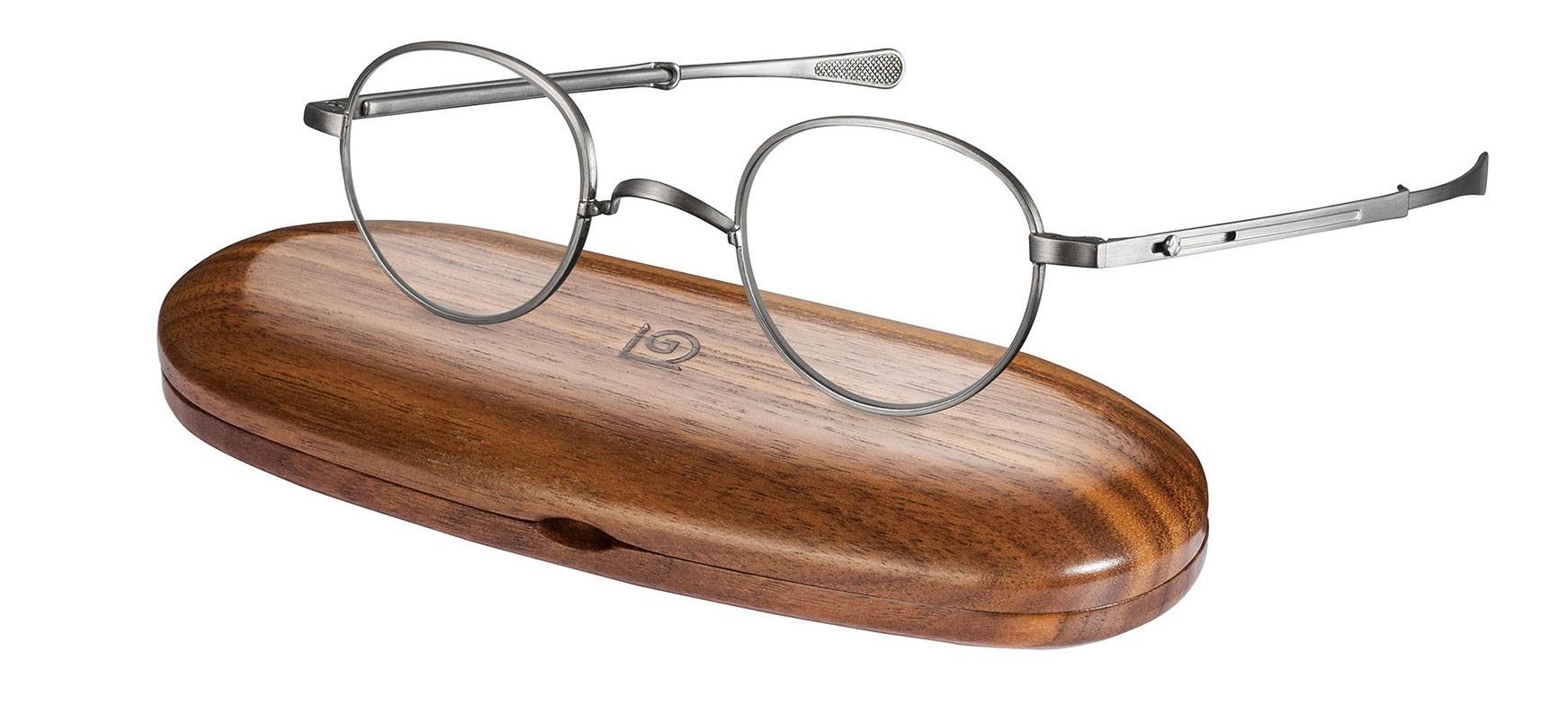 Nahaufnahme von einer Gernot Lindner runden Korrekturbrille mit silbernem Gestell, die auf einem Brillenetui aus Holz liegt.