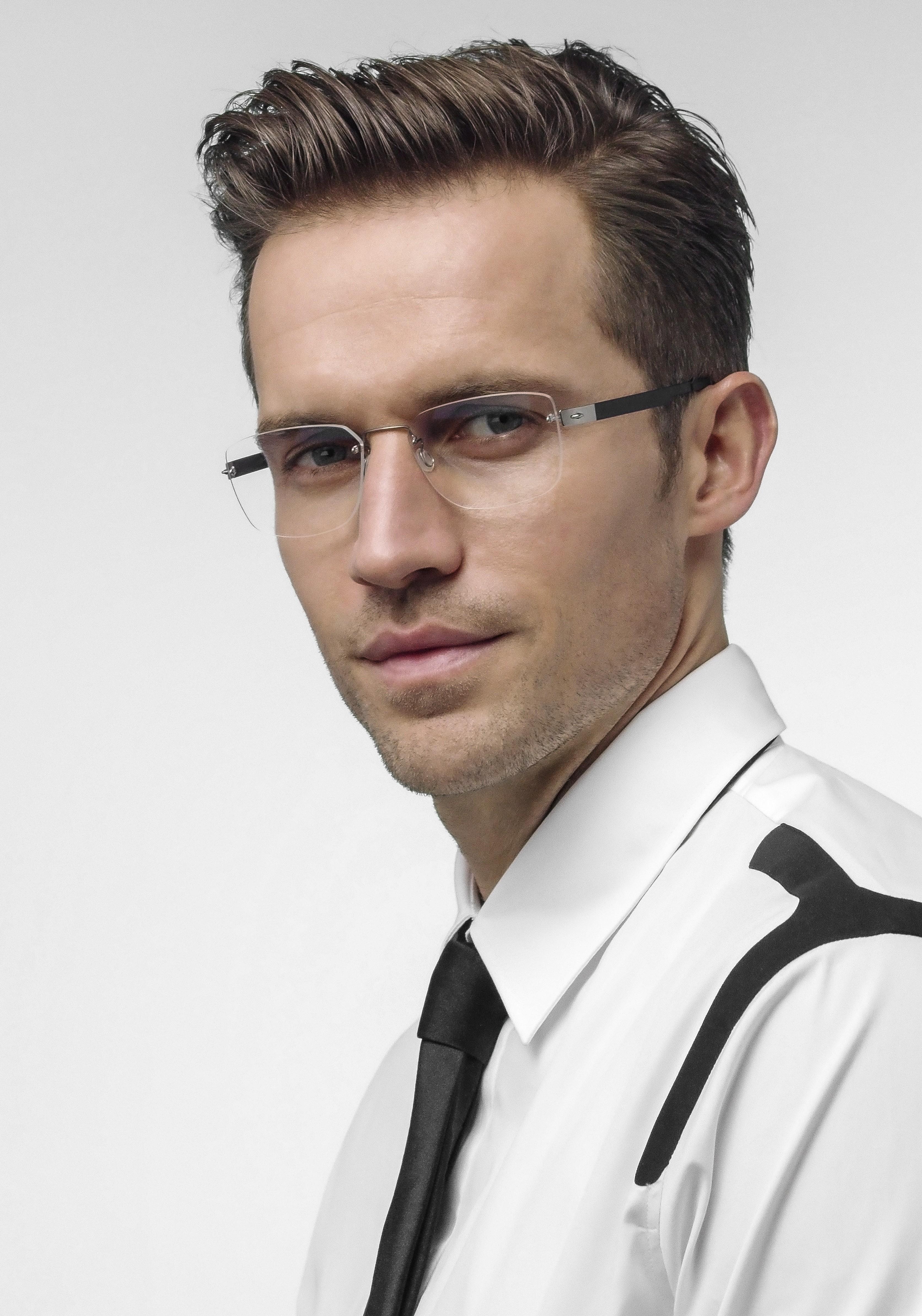 Braunhaariger Mann trägt ein weißes Hemd und eine rahmenlose Korrekturbrille mit dunklen Bügeln und blickt in die Kamera.